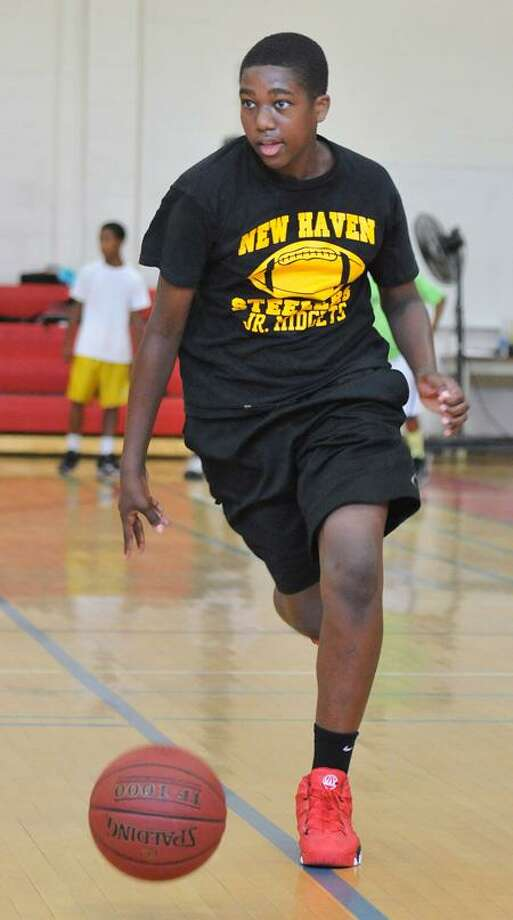 Jordan Townsend, 14, drives down the court during the Skills Camp Inc. basketball camp at Wilbur Cross High.    Peter Casolino/New Haven Register