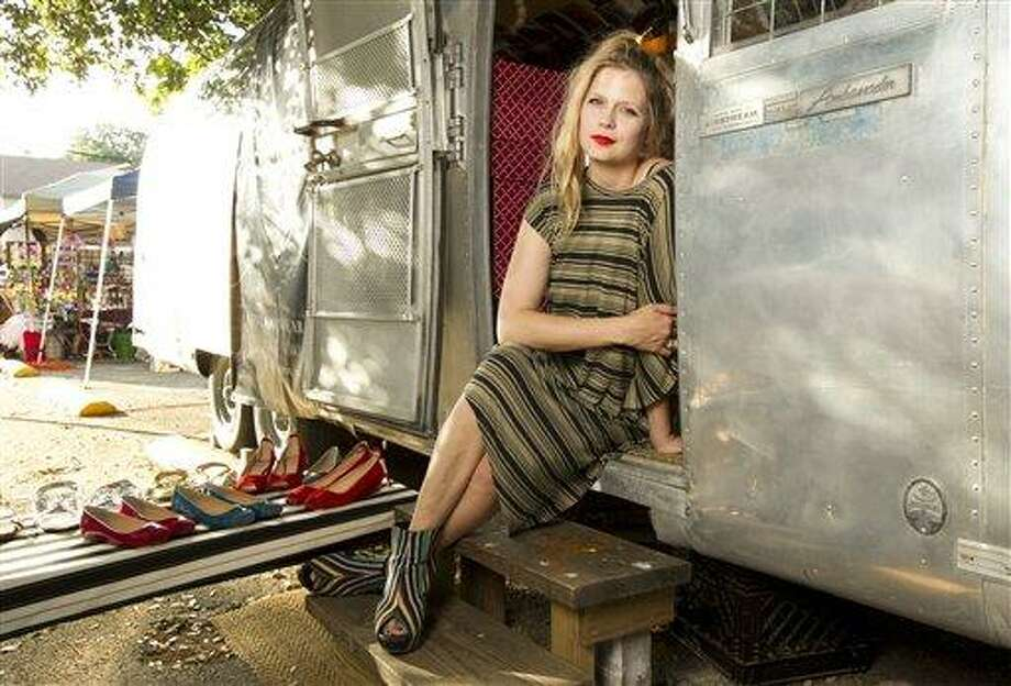 In this photo taken April 5, 2012, Sarah Ellison Lewis, the owner of Bootleg, a shoe trailer with hard-to-find footwear labels poses in Austin, Texas. When former fashion editor Sarah Ellison Lewis wanted to open an upscale, funky shoe boutique in Austin, Texas, she had sticker shock every time she saw the price for a store lease. She worried the hefty rent would limit her ability to turn a profit so she bought a 30-foot trailer, decorated it with vintage wallpaper photography and reclaimed wooden benches and signed a lease on a parking spot between a chic hotel and popular brunch spot in an eclectic neighborhood for a quarter of the cost of a traditional store. (AP Photo/Statesman.com, Jay Janner) Photo: ASSOCIATED PRESS / Austin American-Statesman2012