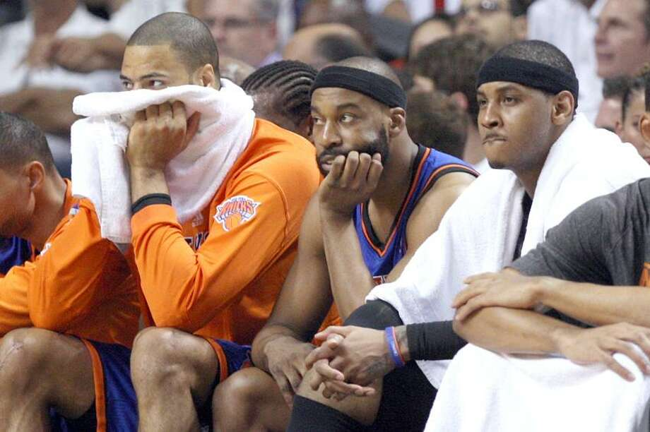 New York Knicks' Tyson Chandler, left, Baron Davis, center, and Carmelo Anthony, right, watch from the bench in the fourth quarter during an NBA basketball game in the first round of the Eastern Conference playoffs in Miami, Saturday, April 28, 2012. The Heat defeated the Knicks 100-67. (AP Photo/Lynne Sladky) Photo: AP / AP