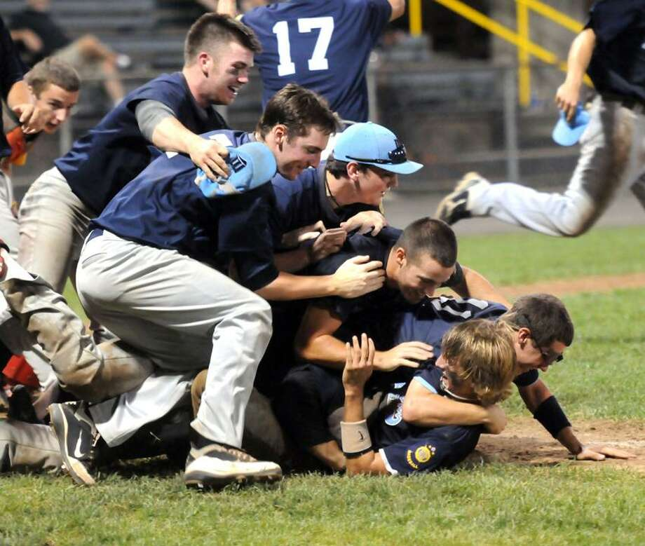 Milford celebrates the winning run by Nick Pinto, second from right, in Friday night's American Legion state championship game at Muzzy Field in Bristol. (Mara Lavitt/New Haven Register)