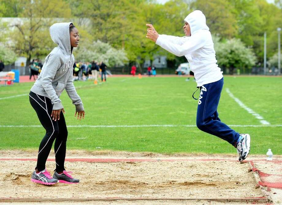 Chaslynn Saucier (left), 15, assists freshman Brianna Rigsbee (right), 15, practicing the long jump during track practice at Wilbur Cross High School in New Haven on 4/23/2012.Photo by Arnold Gold/New Haven Register  AG0466E
