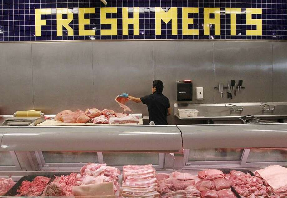 Butcher Freddie Quina cuts meat at Super Cao Nguyen in Oklahoma City, Wednesday, July 25, 2012. The record drought gripping half the country will help push food prices up by 3 percent to 4 percent next year, the U.S. Department of Agriculture said. (AP Photo/Sue Ogrocki) Photo: AP / AP2012
