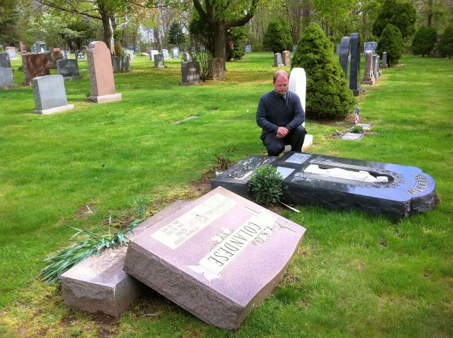 Scott Verespie, general manager St, Lawrence Cemetery in West Haven, show two of the 15 headstones that were knocked over by vandals.  Peter Hvizdak/Register