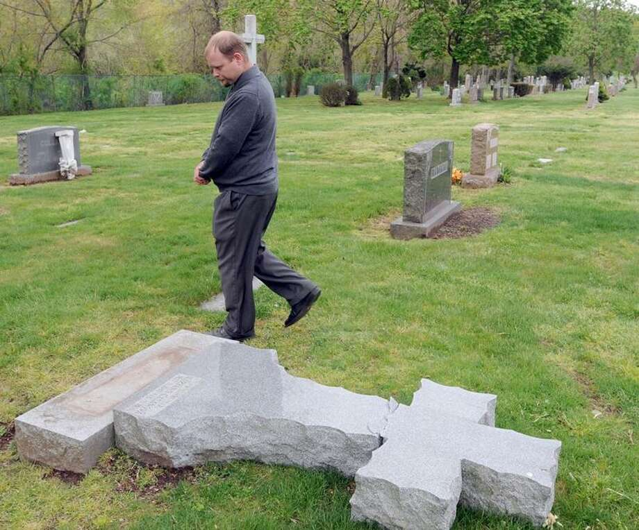 Scott Verespie, general foreman of the St. Lawrence Cemetery in West Haven, walks past one of 15 headstones vandalized at the cemetery. 4/24/12 Photo by Peter Hvizdak / New Haven Register.