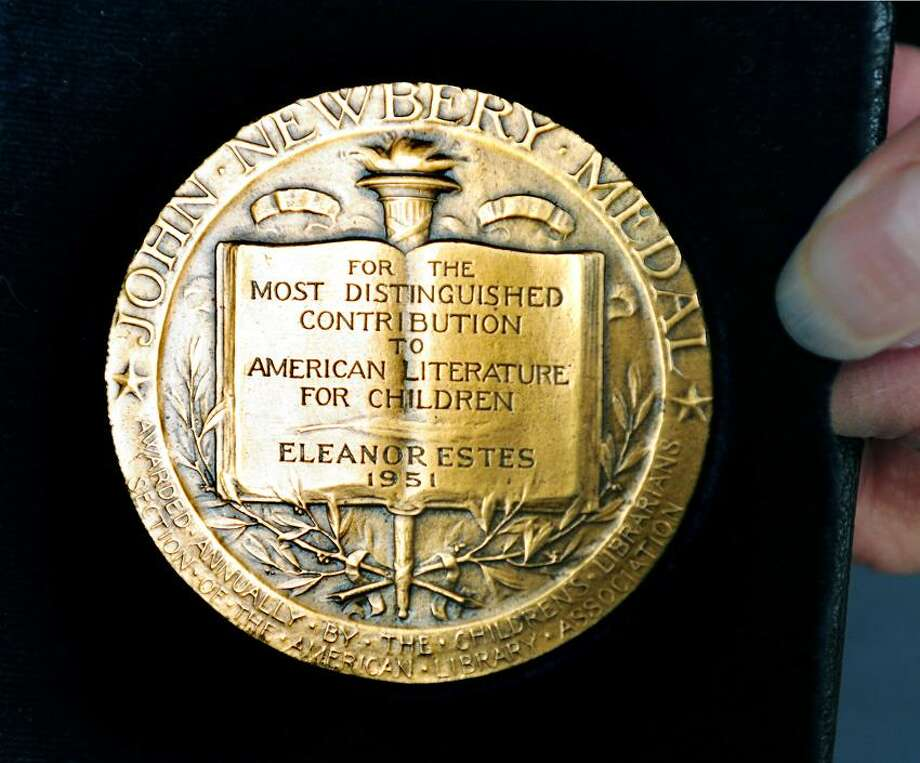 The John Newbery Medal awarded to the late Eleanor Estes in 1951 for the children's book, Ginger Pye, held by her daughter, Helena Estes, is photographed at the Case Memorial Library in Orange. Arnold Gold/New Haven Register