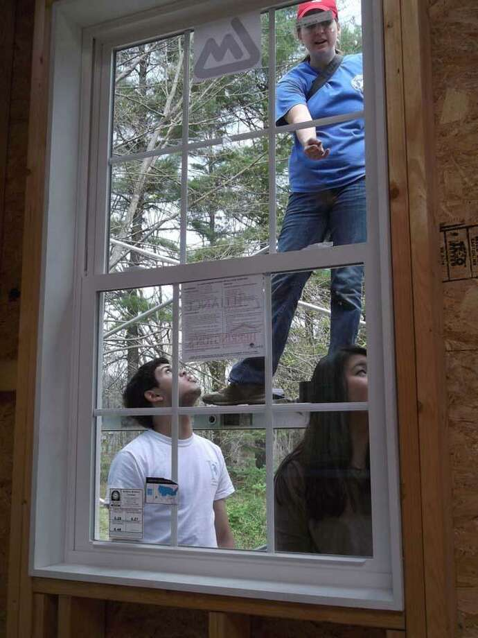 RICKY CAMPBELL/ Register Citizen  Volunteer workers installing windows Saturday at a house project in Canaan were mainly Housatonic Valley Regional High School students learning about non-profits and civic engagement.