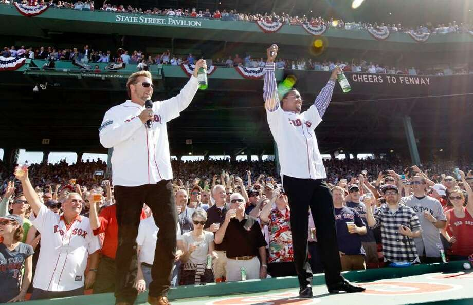 Former Boston Red Sox players Kevin Millar, left, and Pedro Martinez lead the fans in a toast at Fenway Park in Boston, Friday, April 20, 2012, during a celebration of the 100th anniversary of the first regular-season game at the ballpark prior to a baseball game against the New York Yankees. (AP Photo/Elise Amendola) Photo: AP / Copyright: The Associate Press