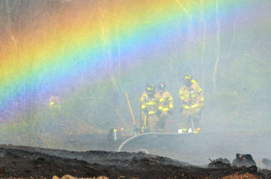 Firefighters at the scene of a brush fire at the Borelli farm off Warner Rd in North Haven appear to be standing under a rainbow. The effect was caused by water vapor from the water being used to fight the fire and smoke refracting light. vm Williams m04.10.12
