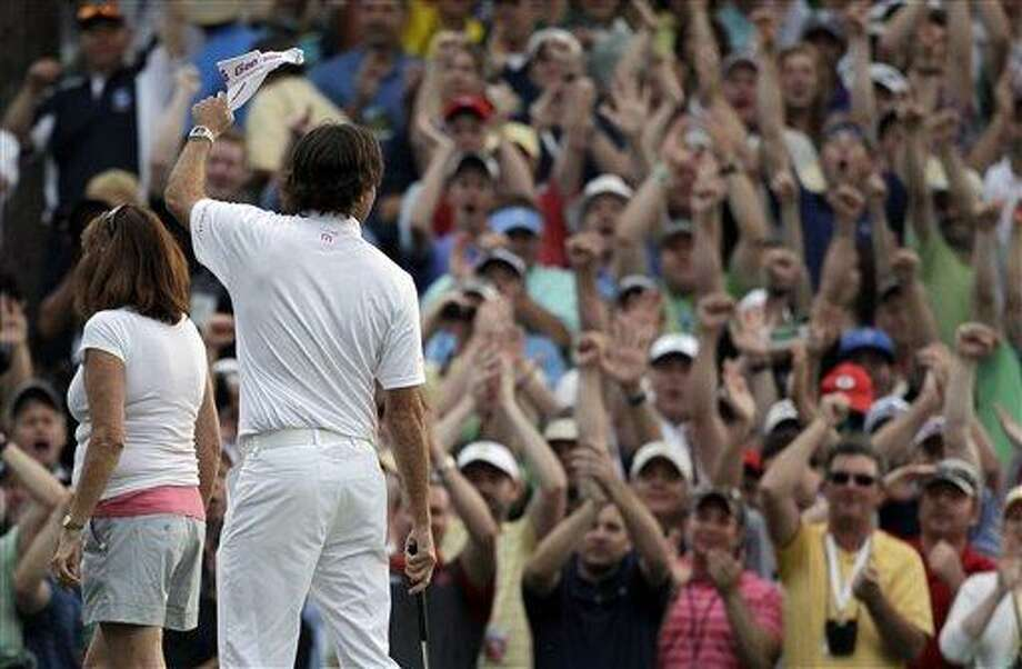 **CORRECTS MOTHERS NAME TO MOLLY** Accompanied by his mother Molly, Bubba Watson raises his cap to spectators after winning the Masters golf tournament following a sudden death playoff on the 10th hole Sunday, April 8, 2012, in Augusta, Ga. (AP Photo/Chris O'Meara) Photo: ASSOCIATED PRESS / AP2012