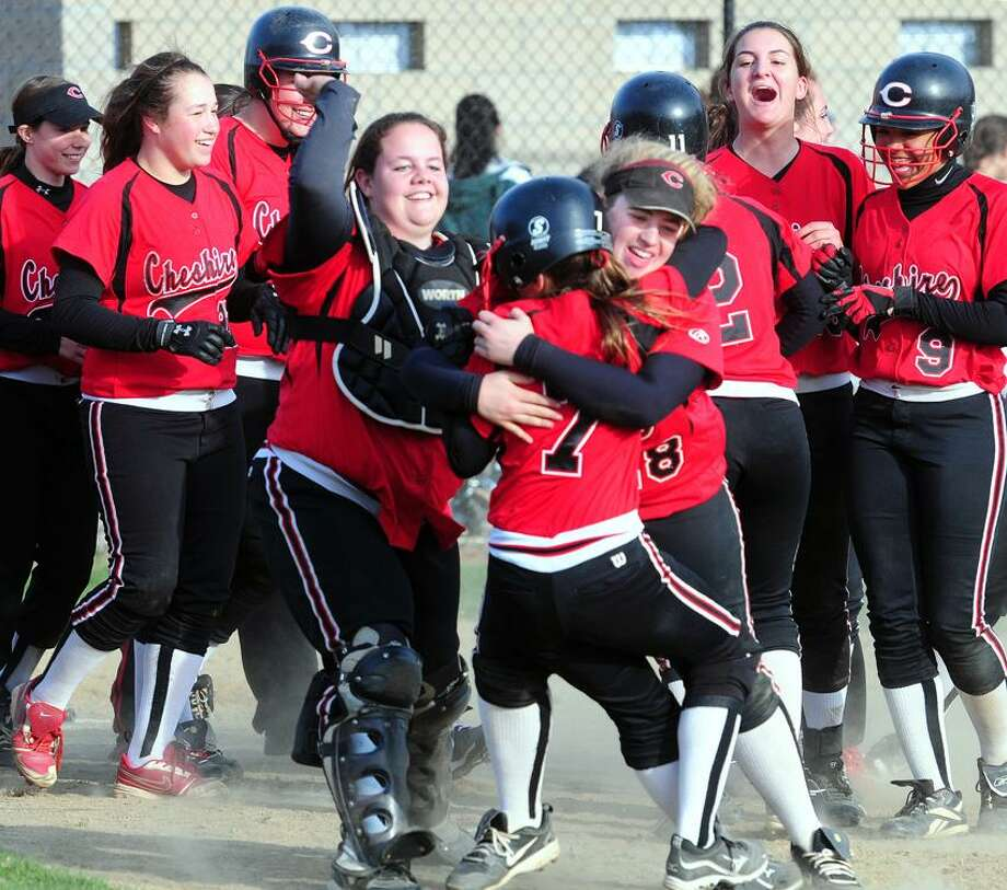 Cheshire's Lauren Fountain, center hugs Kathryn Vitale after the winning run scored in the eighth inning against Guilford. At center left is catcher Kierstyn Bourdeau. Photo by Arnold Gold/New Haven Register