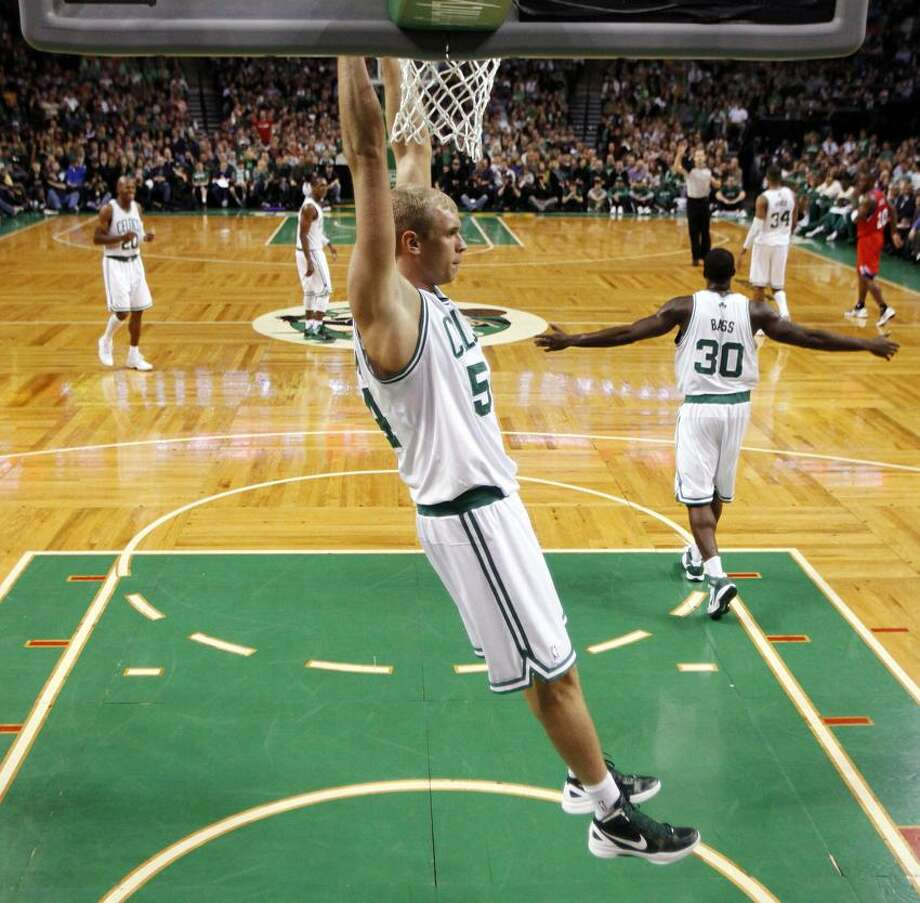 Boston Celtics' Greg Stiemsma, center, hangs from the rim after scoring in the second half of an NBA basketball game against the Philadelphia 76ers in Boston, Sunday, April 8, 2012. The Celtics won 103-79. (AP Photo/Michael Dwyer) Photo: AP / AP2012
