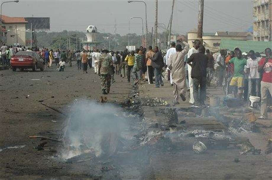 People gather at the site of a bomb explosion at a road in Kaduna, Nigeria Sunday. An explosion struck Sunday in Kaduna central Nigeria that has seen hundreds killed in religious and ethnic violence in recent years, causing unknown injuries as diplomats had warned of possible terrorist attacks over the Easter holiday, police said. Associated Press Photo: AP / AP