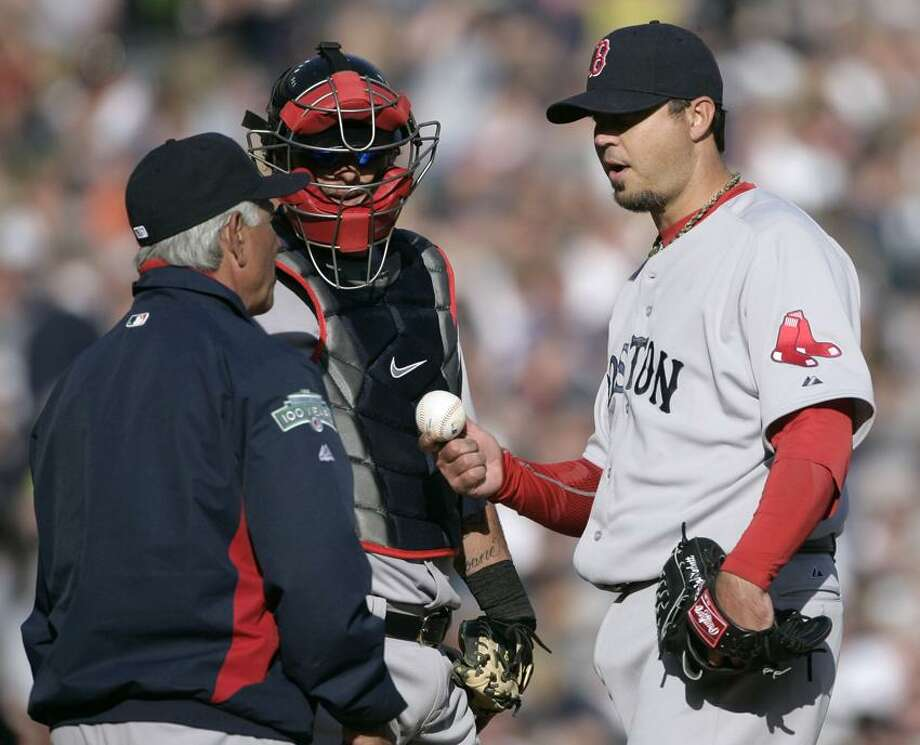 Boston Red Sox starter Josh Beckett, right, gives up the baseball to manager Bobby Valentine, left, as catcher Jarrod Saltalamacchia looks on in the fifth inning of a baseball game Saturday, April 7, 2012, in Detroit. Beckett was relieved after giving up back-to-back home runs to Detroit's Miguel Cabrera and Prince Fielder. (AP Photo/Duane Burleson) Photo: AP / AP2012