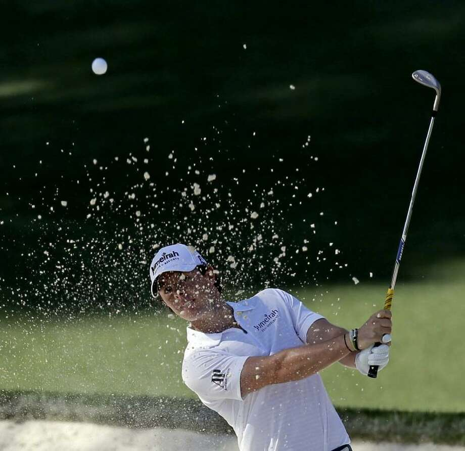 ASSOCIATED PRESS Rory McIlroy hits out of a bunker on the 10th hole during the third round of the Masters golf tournament Saturday in Augusta, Ga. Both McIlroy and Sergio Garcia struggled during the third round on Saturday.