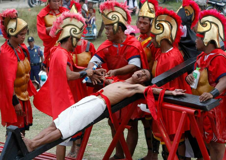 Volunteers dressed as Roman Centurions, drive nails through the palms of an unidentified Catholic devotee in a reenactment of the crucifixion of Jesus Christ on Good Friday at San Pedro Cutud, Pampanga province, north of Manila, Philippines Friday, April 6, 2012. More than two dozen Catholic devotees have themselves nailed on the cross on Good Friday, a practice rejected by the Catholic Church but has become a tourist attraction.(AP Photo/Bullit Marquez) Photo: ASSOCIATED PRESS / AP2012