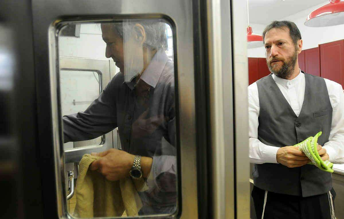 Rabbi Jon-Jay Tilsen of Congregation Beth El-Keser Israel in New Haven (right) watches congregant David Wright of Hamden tend to baking matzo in the stove during a baking session with congregants in the kitchen of the synogogue Friday. (Photo by Peter Hvizdak/ New Haven Register)