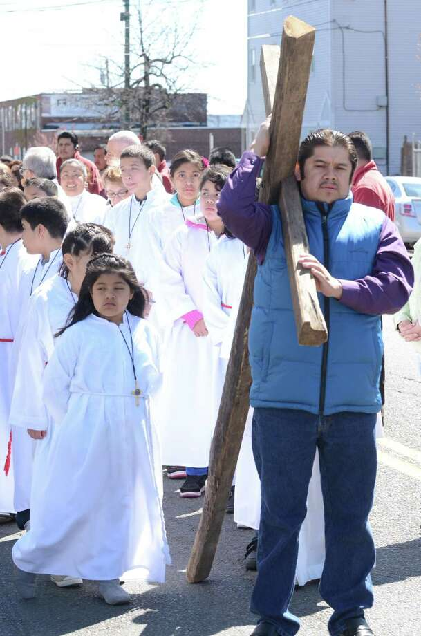Andres Garcia shoulders the cross for the start of the procession at St. Rose of Lima Church in New Haven. V.M. Williams/Register