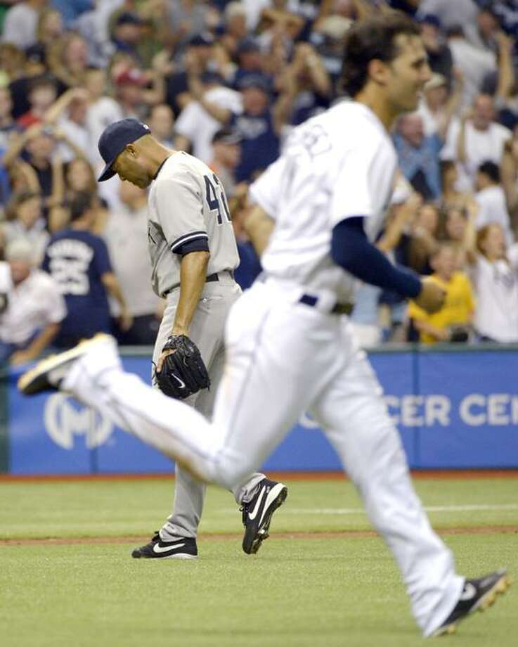 New York Yankees reliever Mariano Rivera, left, walks off the mound as Tampa Bay Rays' Sean Rodriguez runs onto the field after Rivera gave up the game-winning RBI single to Carlos Pena in the bottom of the ninth inning of a baseball game in St. Petersburg, Fla., Friday, April 6, 2012. The Rays won 7-6.(AP Photo/Phelan M. Ebenhack) Photo: AP / AP2012