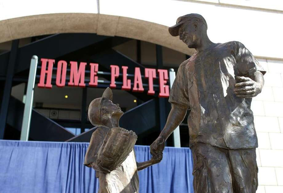 The Fan Statue is displayed after being unveiled during a dedication ceremony on Thursday, April 5, 2012, in Arlington, Texas. The statue is of Ranger's fan Shannon Stone, who died after falling out of the stands trying to catch a ball in 2011, and his son Cooper. (AP Photo/Sharon Ellman) Photo: AP / AP2012