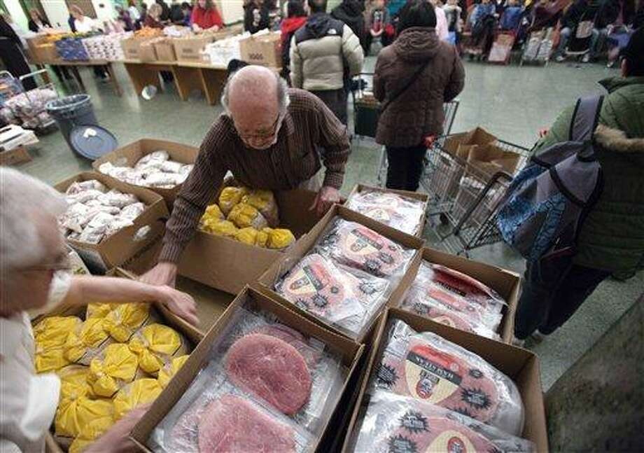 Paul Farris, second from left, of Boston, distributes hams and chickens March 29 in the Franciscan Food Center food pantry at St. Anthony Shrine in Boston. Ham prices have been higher than usual for the past two years because the cost of pig feed has gone up. Associated Press Photo: AP / AP