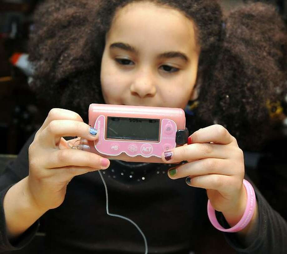 Michelle Johnson, 8, at home in Guilford. Michelle has Type 1 diabetes and wears a pastel pink insulin pump. Mara Lavitt/New Haven Register