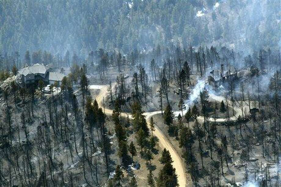 In this March 27 photo, one home stands untouched at left while another home at right smolders after burning in the Lower North Fork Wildfire in the foothills community of Conifer, Colo., southwest of Denver. Emergency officials told confused residents not to worry after they reported a fire on the outskirts of Denver, including at least two residents who later were found dead in their burning home. Associated Press Photo: AP / AP2012