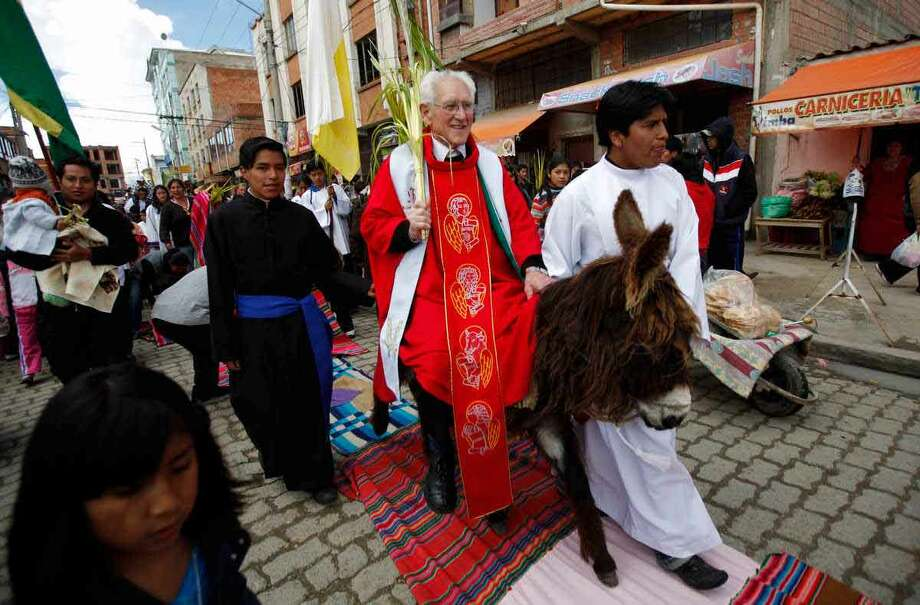 Catholic priest Sebastian Obermaier rides on a donkey holding palm fronds during a Palm Sunday procession before giving a Mass in El Alto, Bolivia, Sunday. For Christians, Palm Sunday marks Jesus Christ's entrance into Jerusalem, when his followers laid palm branches in his path, prior to his crucifixion. Associated Press Photo: ASSOCIATED PRESS / AP2012