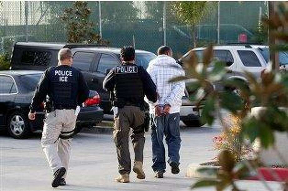 In this March 30, 2012 photo, Immigration and Customs Enforcement (ICE) agents take a suspect into custody as part of a nationwide immigration sweep in Chula Vista, Calif. Federal officials say they arrested more than 3,100 immigrants convicted of serious crimes and fugitives in a six-day nationwide sweep. Officials at U.S. Immigration and Customs Enforcement say the sweep included every state and involved more than 1,900 of the agency's officers and agents. (AP Photo/Gregory Bull)