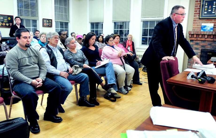 Michael Majewski, seated far left, listens to Francis Klos III, right, give testimony during a zoning board meeting concerning their gun shop, Woodbridge Firearms Trading Post, at Woodbridge Town Hall. Photo by Arnold Gold/Register
