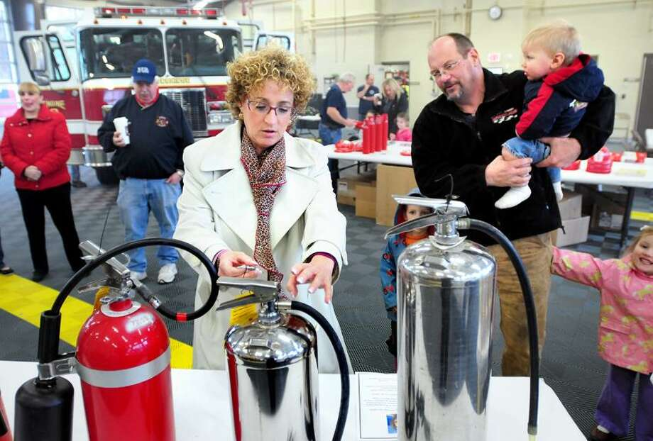 Barbara Block, center, of Woodbridge shows Bob Parker and his children how to use a fire extinguisher during a fire safety and education day at the Woodbridge Fire Department.  Block's daughter, Eva, died in a house fire while away at Marist College earlier in the year. Arnold Gold/Register