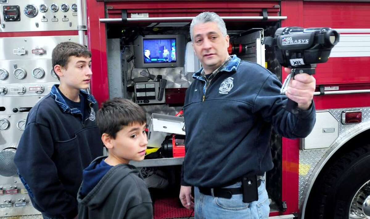 Volunteer firefighter Jim Kaoud, right, of Woodbridge shows his sons, R.J., left, 14, and Joey, center, 10, how an infrared camera works during a fire safety and education day at the Woodbridge Fire Department. Arnold Gold/Register