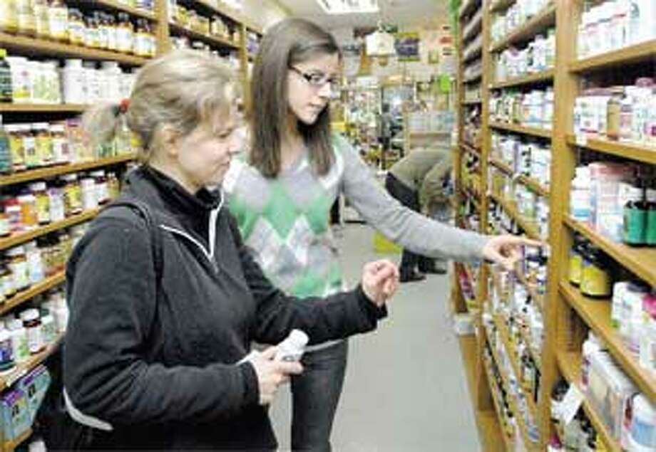 Barbara Cavrell, left, of Madison gets help from Shana Waters at Foodworks in Guilford. (Arnold Gold/Register)