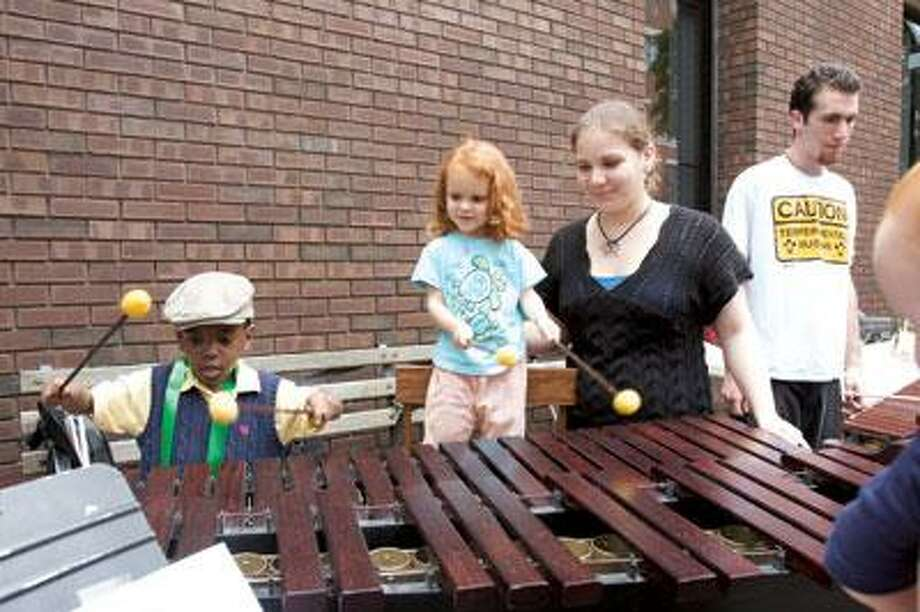 Youngsters at last year's event take their turn at the Neighborhood Music School's instrument petting zoo. (Judy Sirota Rosenthal)
