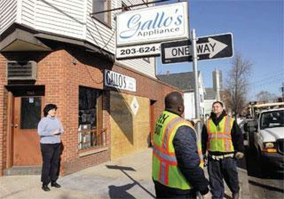 Marie Gallo watches Wednesday as city workers Kevin Rose, center, and Danny Cruz replace the one-way sign outside her store on State Street in New Haven. Plywood covers the area where a car struck the storefront Tuesday. (Mara Lavitt/Register)