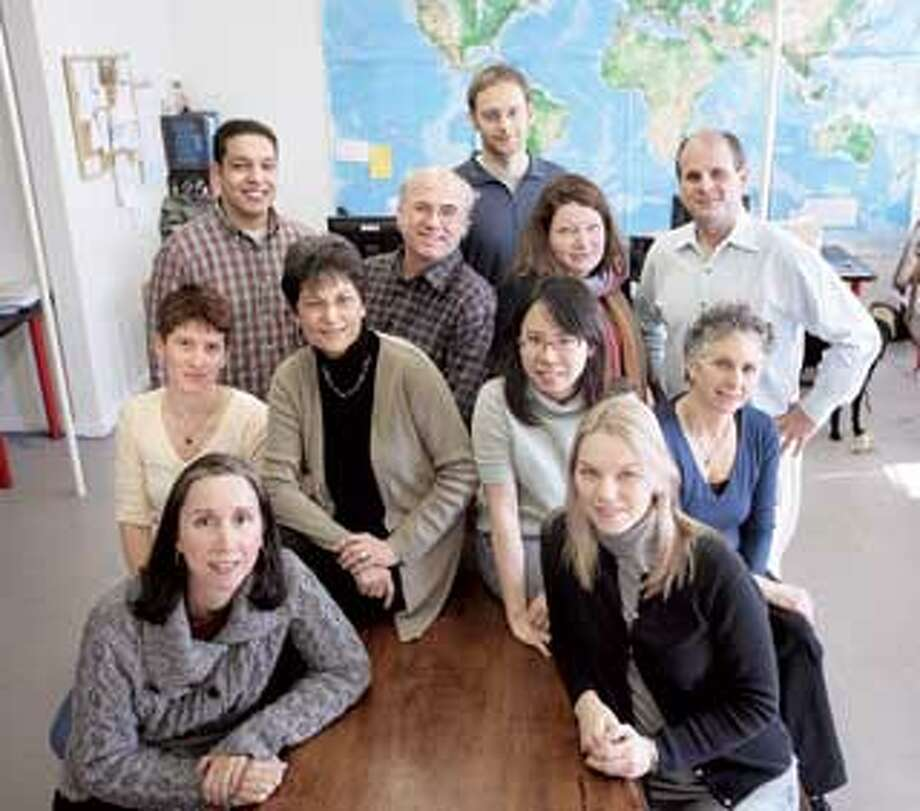Members of Innovations for Poverty Action in New Haven include Kareem Haggag, back row left, David Lindsay, Jacob Appel, Delia Welsh, founder Dean Karlan; middle row left, Becca Lowry, Kathleen Viery, Yating Scuang, Wendy Lewis; front row left, Lisa Carter and Daiva Latifi. (Peter Casolino/Register)