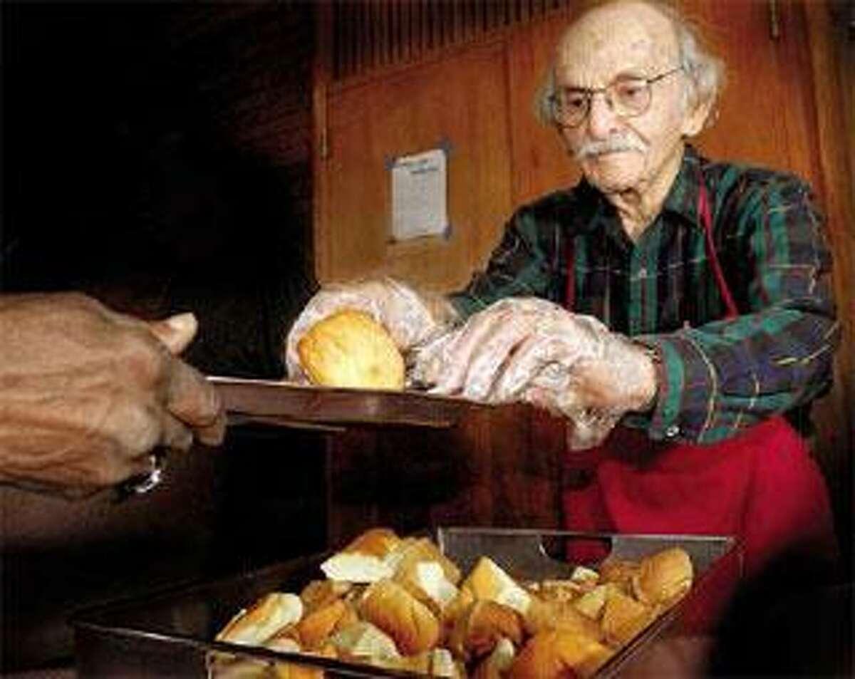 Stan Leavy serves bread at the Community Soup Kitchen in New Haven. (Melanie Stengel/Register)