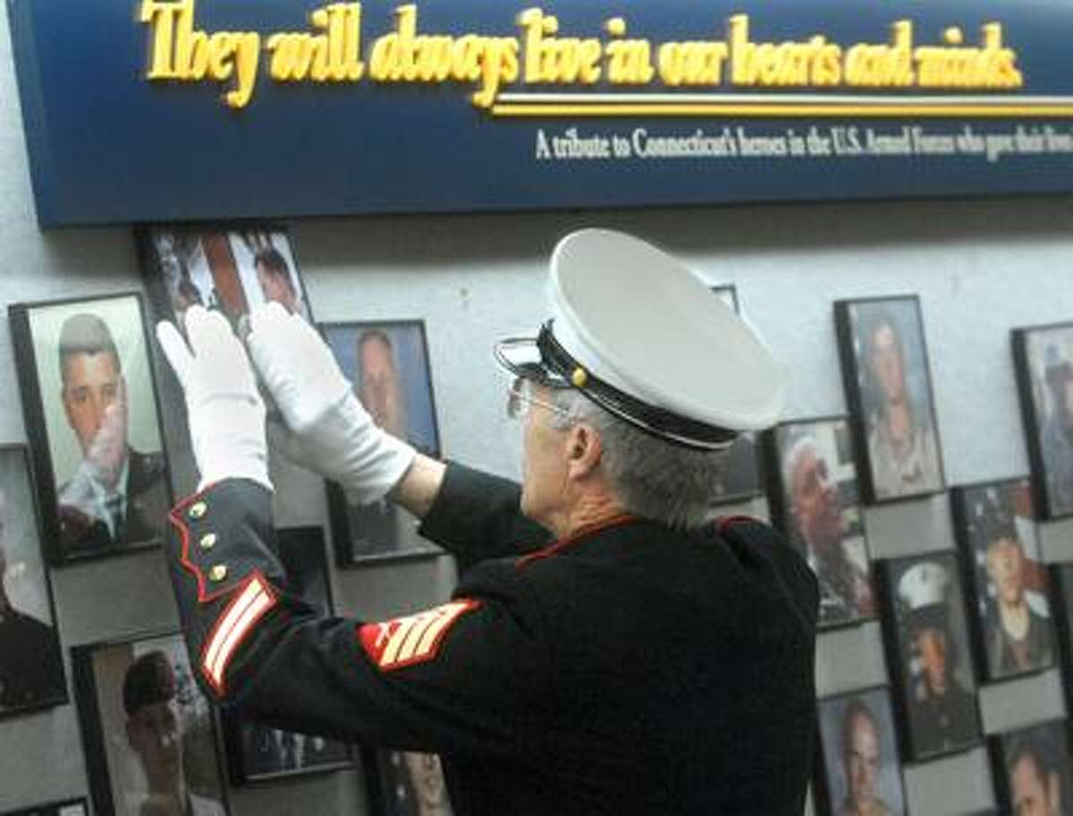 US Marine Corps Sgt. Don Hauser hangs a photograph of Army Capt. Benjamin Sklaver, of Hamden, on the Connecticut Wall of Honor at the Legistlative Office Building in Hartford. (Brad Horrigan/Register)