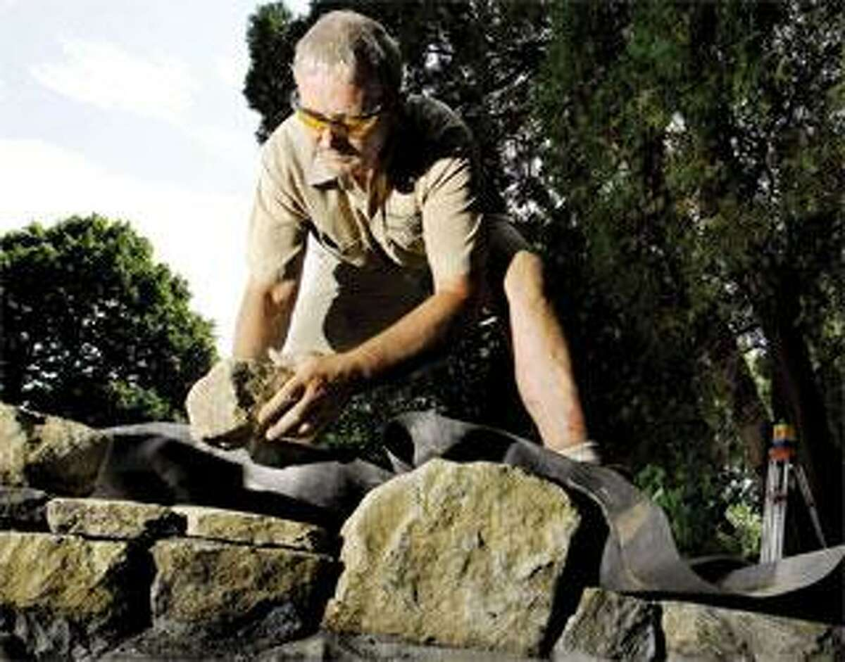 Stone wall craftsman Andrew Pighills builds a mortared stone wall for a pond at a Madison house. (Peter Hvizdak/Register)