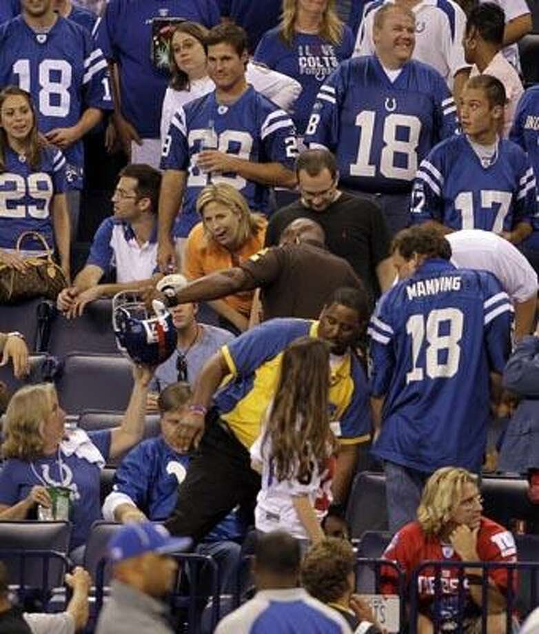 A security officer retrieves the helmet of New York Giants running back Brandon Jacobs from the stands during an NFL football game against the Indianapolis Colts in Indianapolis, Sunday, Sept. 19, 2010. Jacobs apologized for unintentionally throwing his helmet into the stands in the third quarter Sunday night in the Giants' loss to the Indianapolis Colts. (AP Photo/Darron Cummings) Photo: AP / AP