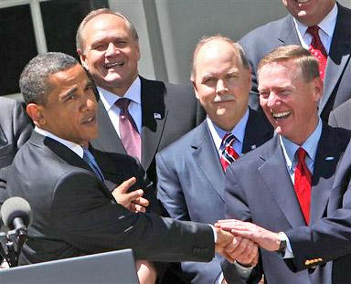 President Barack Obama, left, reaches out to shakes hands with Ford Chief Executive Officer Alan, Mulally, right, as Chrysler CEO, Bob Nardelli, second from the left, and General Motors President, Fritz Henderson, second from the right, look on, Tuesday, May 19, 2009, in the Rose Garden of the White House in Washington during an announcement new fuel and emission standards for cars and trucks. (AP Photo/Pablo Martinez Monsivais)