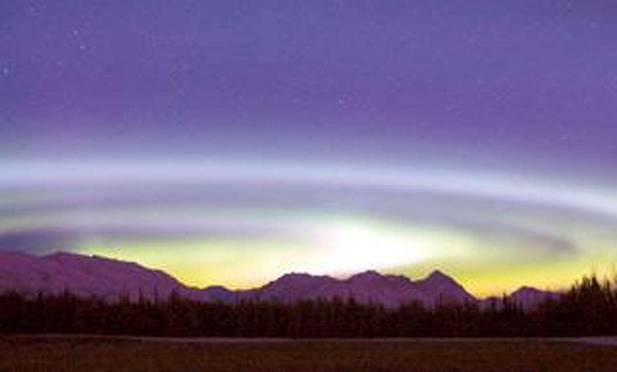 The aurora borealis spins above the Talkeetna Range and a hay field on Farm Loop Road near Palmer, Alaska. (Associated Press photos)