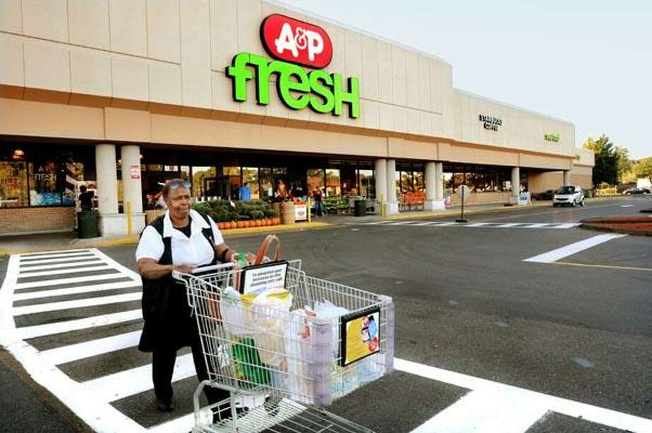Mary Ellen Scott, of New Haven, pushes her grocries to the car from the A&P supermarket in Branford. The stores are scheduled to close in November. (Melanie Stengel/Register)