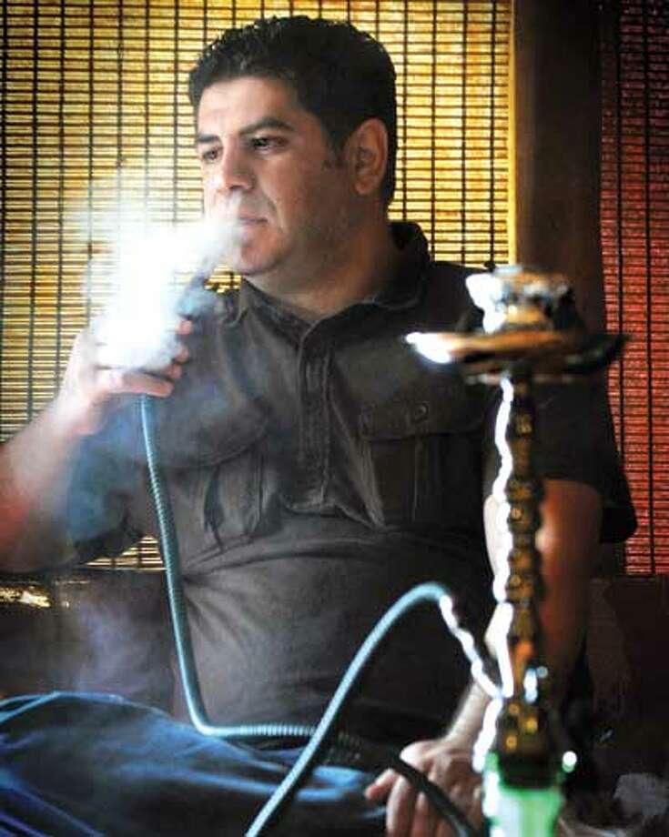Sammer Karout smokes a hookah at his Olive Tree Hookah Lounge in Milford. (Melanie Stengel/Register)