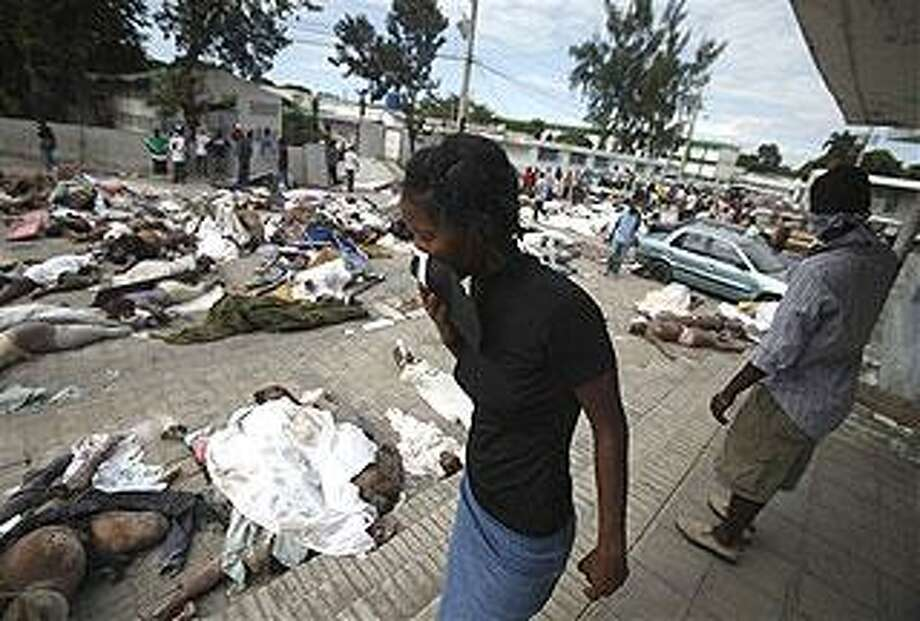 A woman looks for a body among hundreds earthquake victims outside the morgue in Port-au-Prince, Haiti, Thursday, Jan. 14, 2010. A 7.0-magnitude earthquake struck Haiti Tuesday. (AP Photo/Ariana Cubillos)
