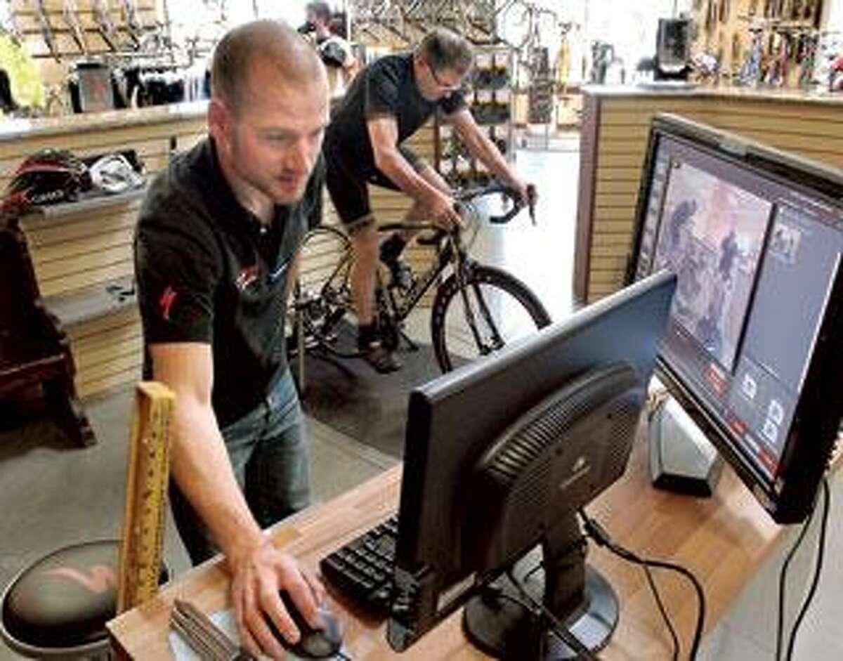 Greg Ciocci of Zane's Cycles in Branford works with cyclist Augustine Filomena of New Haven. (Mara Lavitt/Register photos)