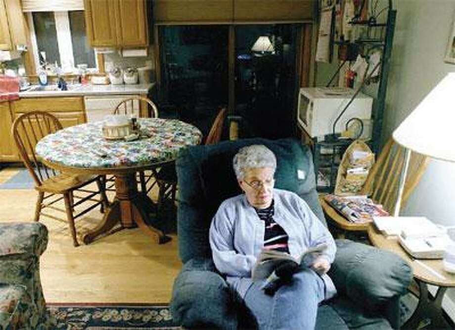 Laudano does a crossword puzzle in her section of the house she shares with her family. (Arnold Gold/Register)