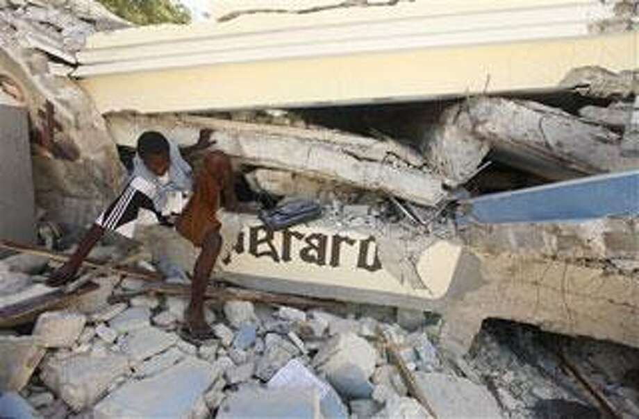 A man looks through the collapsed rubble of St. Gerard Church and School in Port-au-Prince, Thursday, Jan. 14, 2010. Several students and teachers died when the building collapsed after a 7.0-magnitude earthquake hit Haiti on Tuesday. (AP Photo/Gerald Herbert)