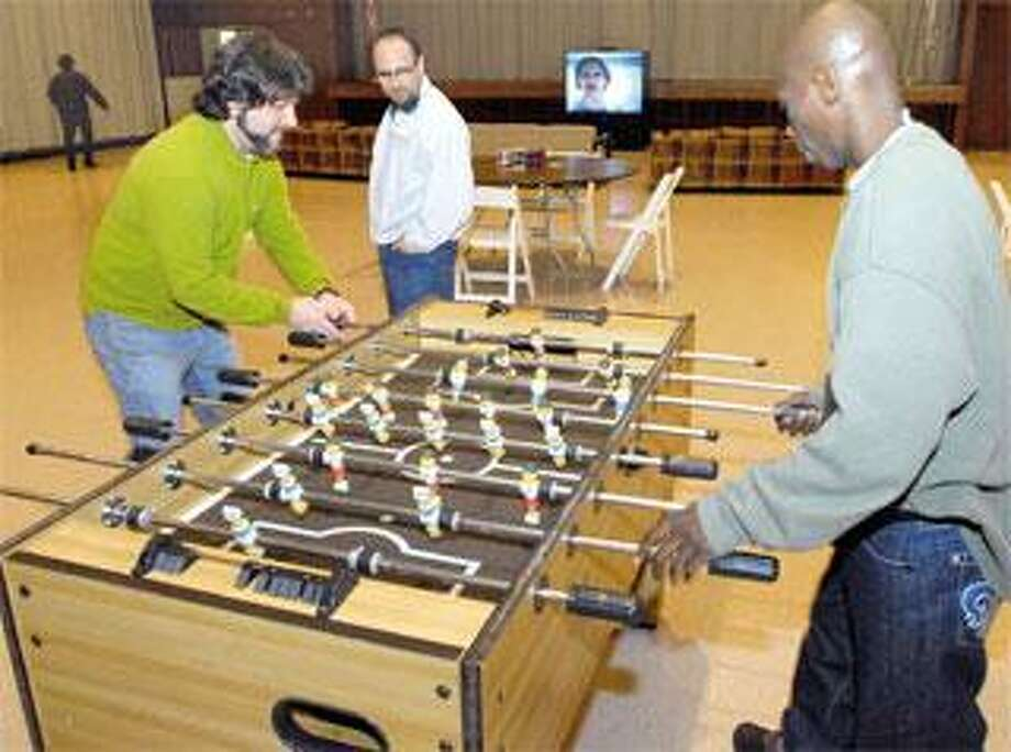 Volunteer David Axman, left, and guest Alvin Murphy play a game of Foosball Monday night at CongregationMishkan Israel in Hamden as volunteer David Chevan keeps an eye on the action. The synagogue is the first of 16 houses of worship to begin taking in overflow from New Haven's Columbus House shelter. (Mara Lavitt/Register)