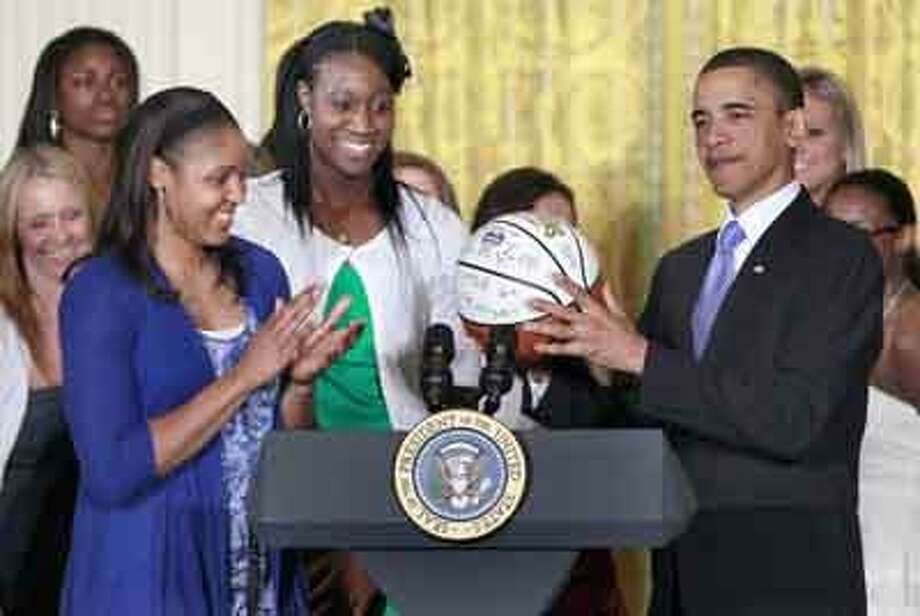 President Barack Obama is presented with an autographed basketball by Tina Charles, center, and Maya Moore, second left, as he honored the 2010 NCAA champion University of Connecticut women's basketball team in the East Room of the White House in Washington, Monday, May 17, 2010. (AP Photo/Charles Dharapak) Photo: AP / AP