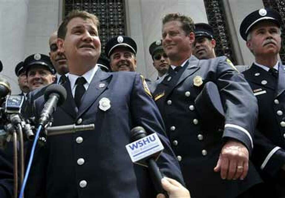 """Frank Ricci, left, lead plaintiff in the the """"New Haven 20"""" firefighter reverse discrimination case speaks to the media outside of Federal Court in New Haven, Conn., Monday June 29, 2009. The Supreme Court ruled in a 5-4 decision that white firefighters in New Haven, Conn., were unfairly denied promotions because of their race, reversing a decision that high court nominee Sonia Sotomayor endorsed as an appeals court judge. (AP Photo/Jessica Hill)"""